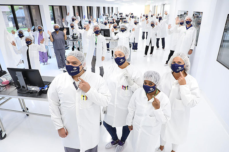 "A large room of scientists in lab coats wearing navy blue masks with the word ""Eagle"" and mask-shaped usa flag pins that read ""hero"". 4 of the scientists in front are point at their masks"