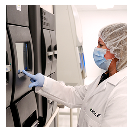 A female scientist using a large black machine