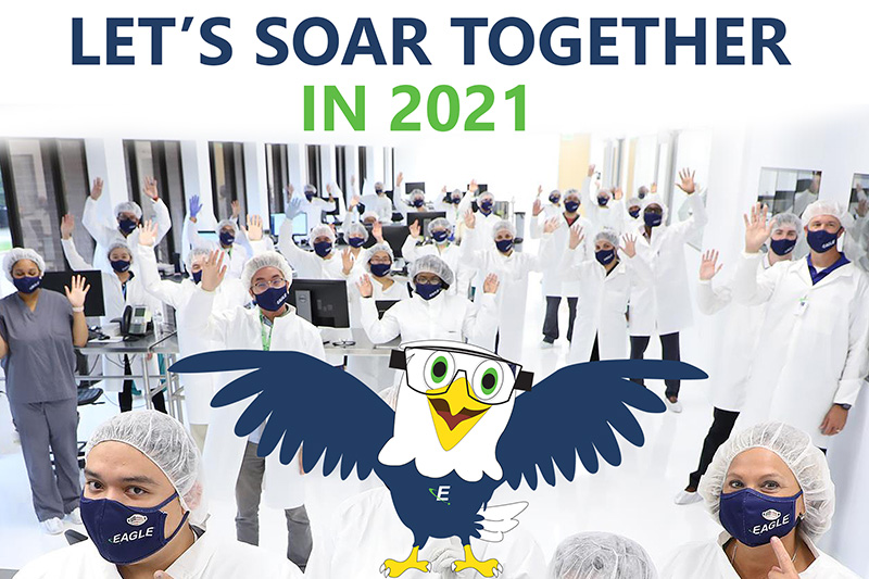 "A group of about 50 Eagle scientists with their hands in the air. They're wearing white lab coats and navy blue Eagle Masks. An Eagle cartoon character wearing navy blue with the Eagle ""e"" emblem logo on his chest. Text reads: ""Let's Soar together in 2021"""