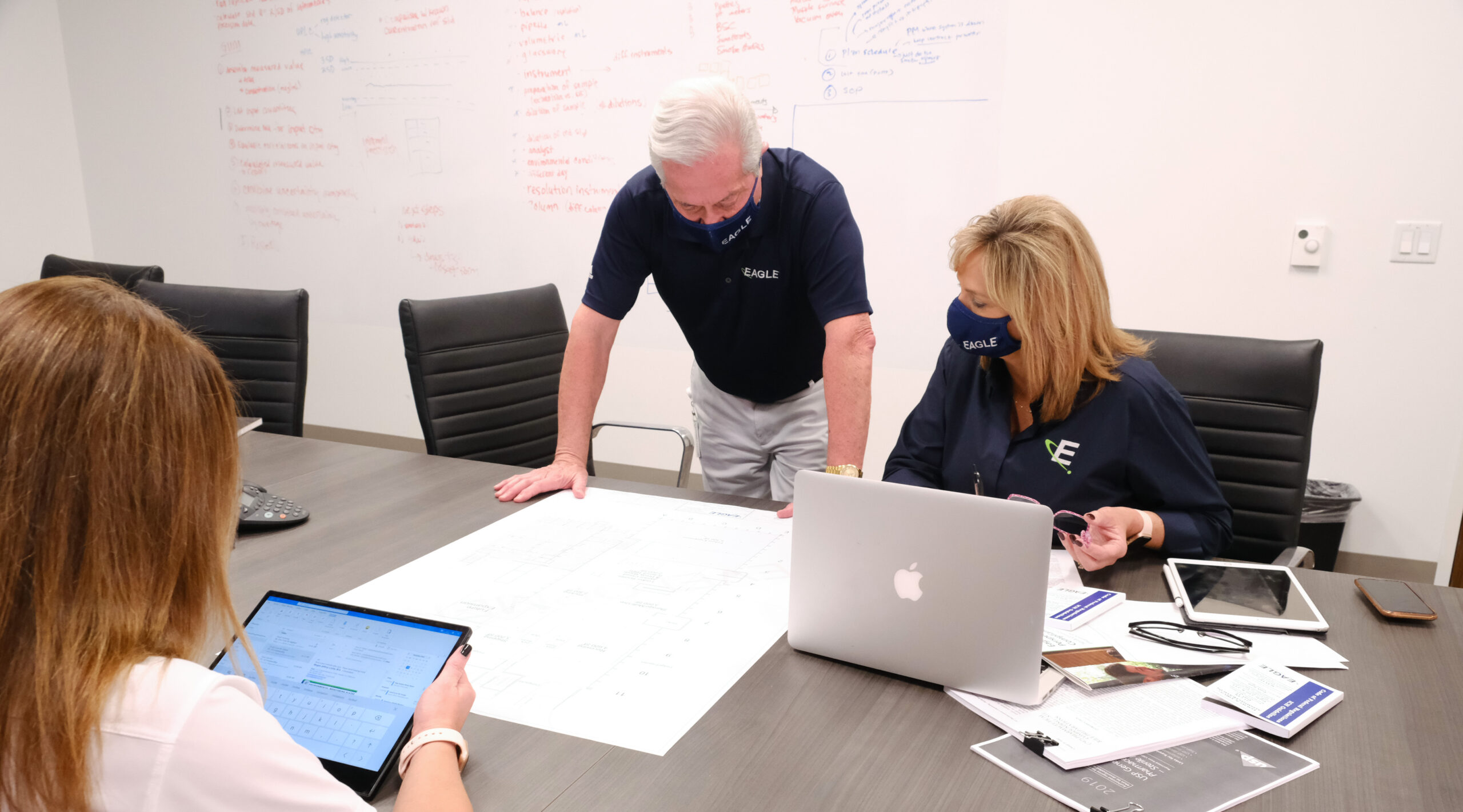 3 Eagle consultants at a table with a blueprint and other paperwork and a computer. One consultant looking at a tablet.