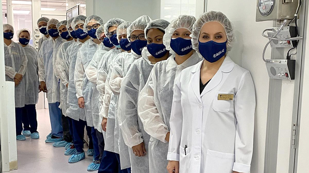 A line of about 20 people in lab coats, hairnets, and navy blue Eagle masks