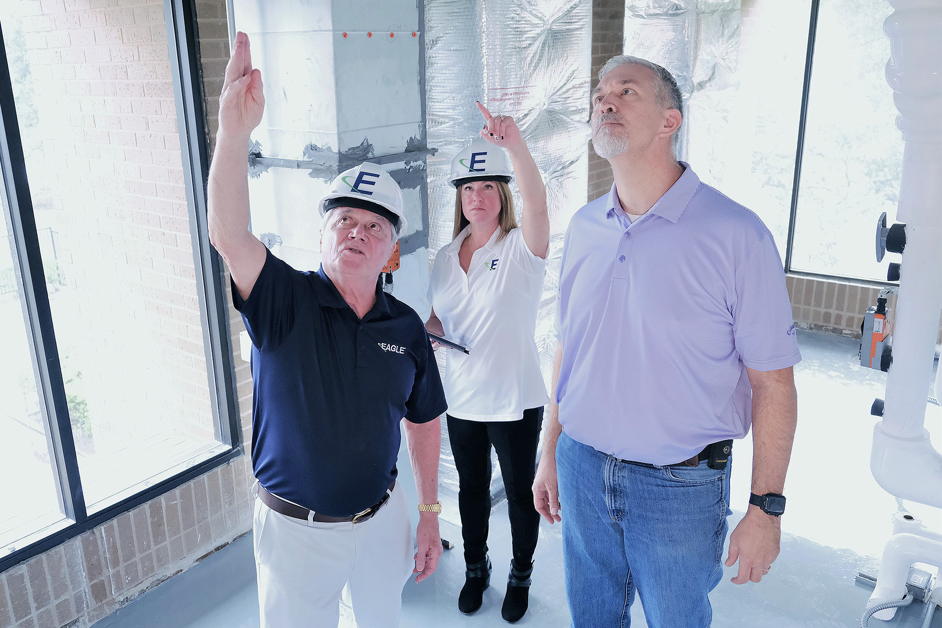 Eagle consultants standing with a man wearing a purple polo shirt. Consultants, a white male and a white female are pointing towards the ceiling. They're standing in an unfinished room under construction