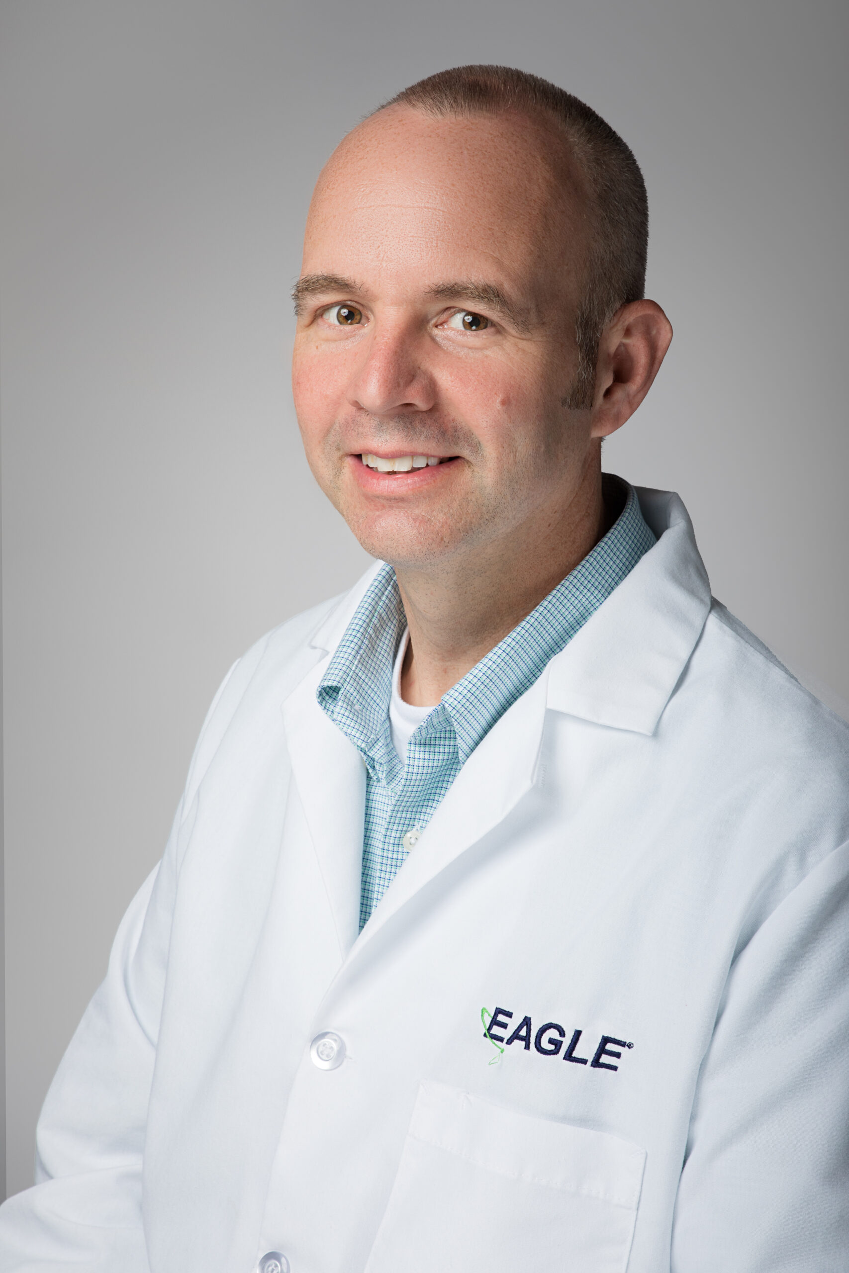 Director of Operations Frank Allen smiles while wearing an Eagle lab coat.