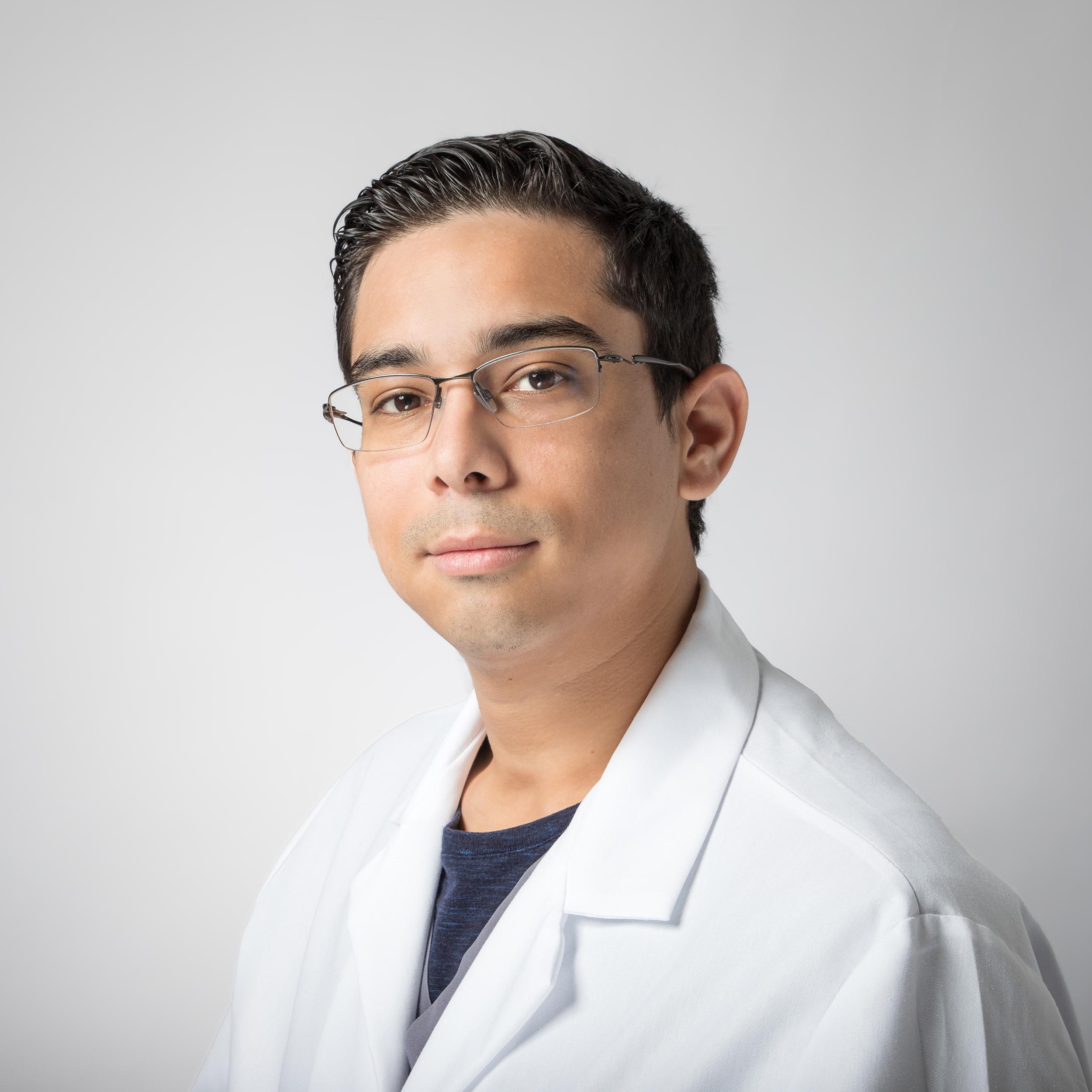 Microbiology Supervisor Christian Jimenez smiles while wearing a white Eagle lab coat.